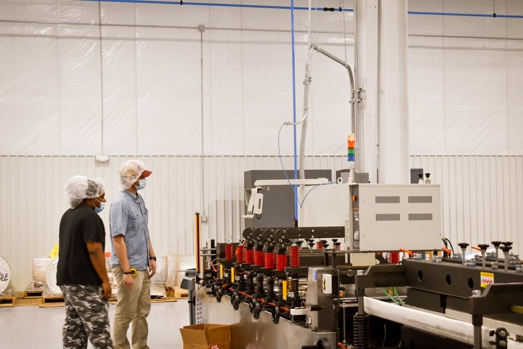 Another image of Lee Duncan and Toreze Jones inspect machine from side
