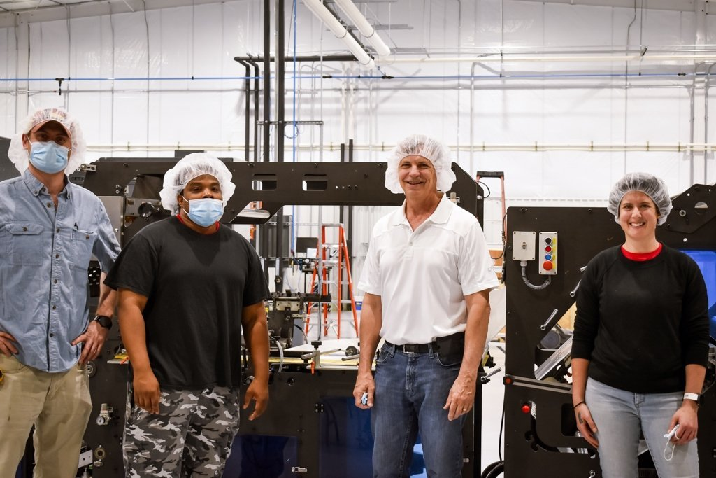 Lee Duncan, Toreze Jones, Tim Mages, and Katherine O'Brien in front of machine